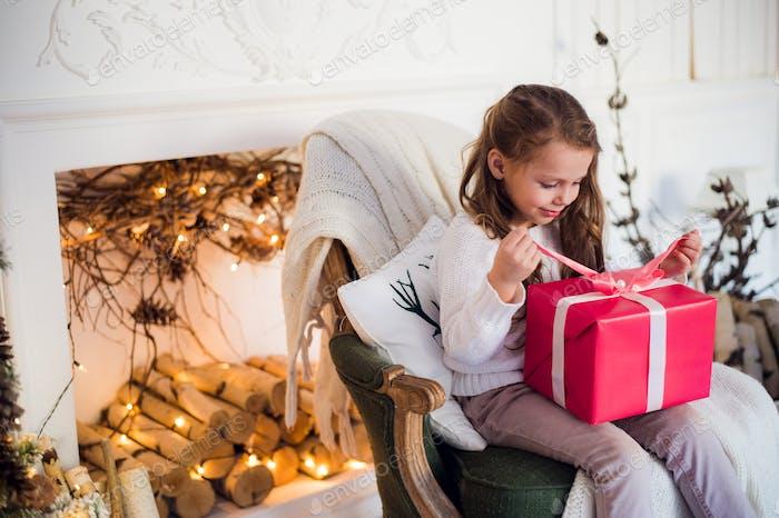 Happy girl Eröffnung Weihnachtsgeschenke durch einen dekorierten Kamin in gemütlichem Licht Wohnzimmer am Weihnachtsabend