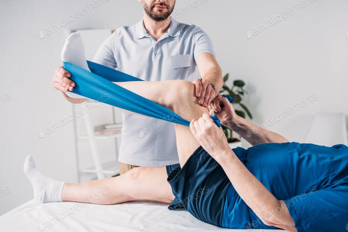 cropped shot of rehabilitation therapist assisting senior man exercising with rubber tape on massage