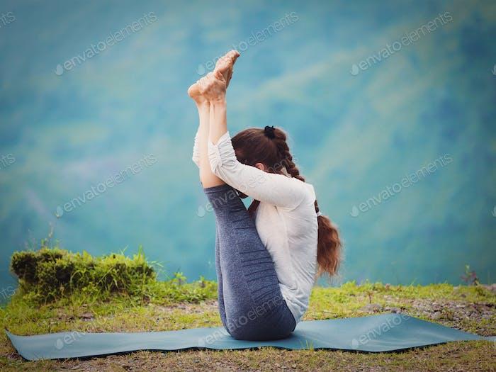 Woman practices yoga asana Urdhva mukha paschimottanasana