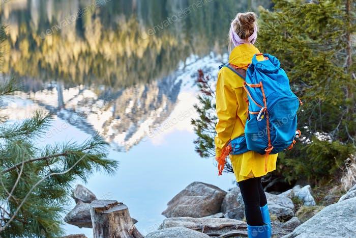 Rückansicht einer Touristin steht auf Steinen im Bergland, bewundert die Reflexion von Bäumen und m