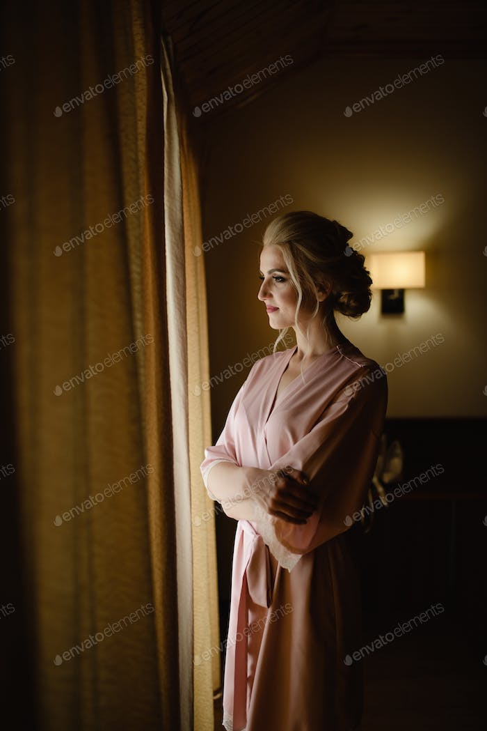 Beautiful blonde girl in a pink bathrobe looks out the window.