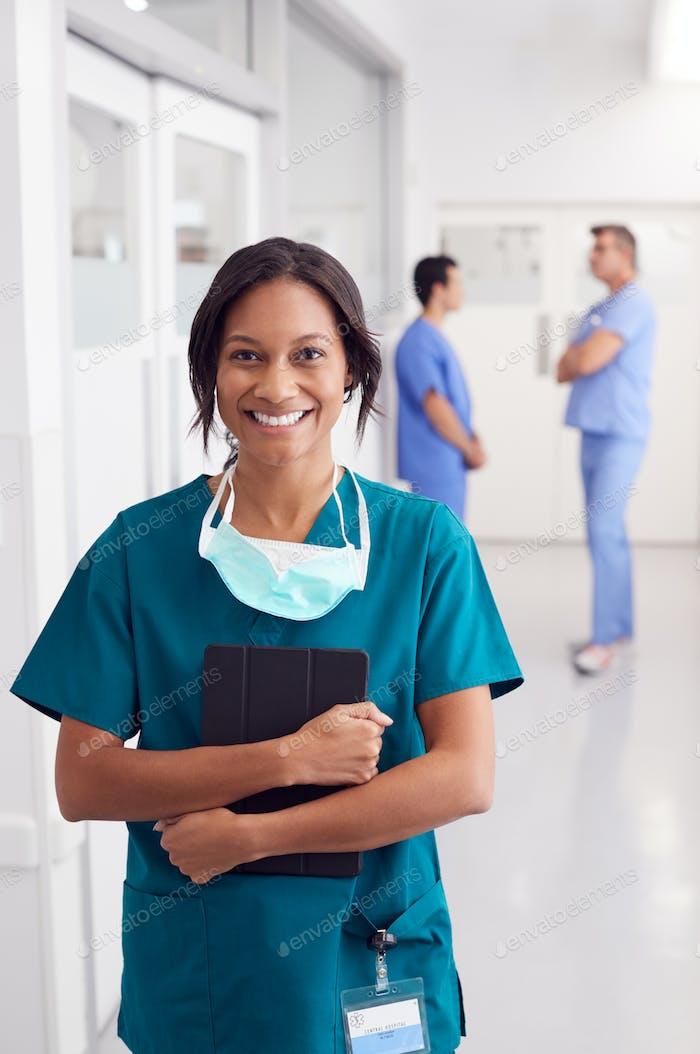 Portrait Of Smiling Female Doctor Wearing Scrubs In Hospital Corridor Holding Digital Tablet