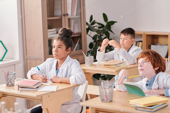 Youthful serious mixed-race girl of elementary age in whitecoat making notes