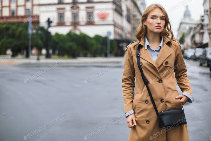 Young beautiful woman in trench coat with little black cross bag