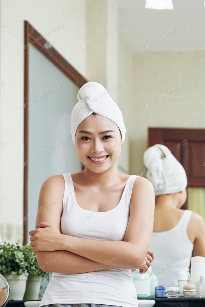 Happy woman in towel standing in bathroom