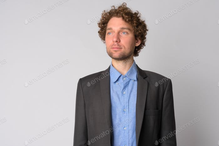 Portrait of handsome businessman with curly hair thinking