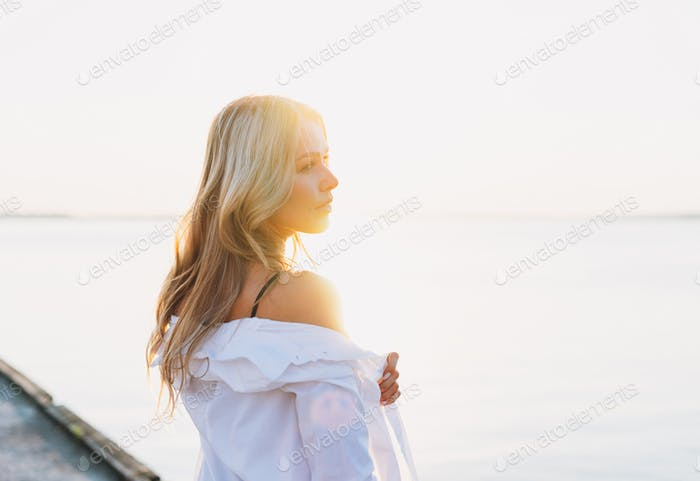 Beautiful blonde young woman in white shirt on pier on sunset