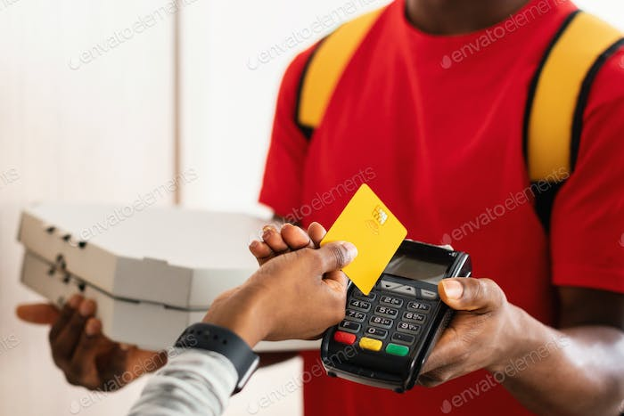 Unrecognizable Customer Paying Courier Putting Credit Card To Terminal Indoors