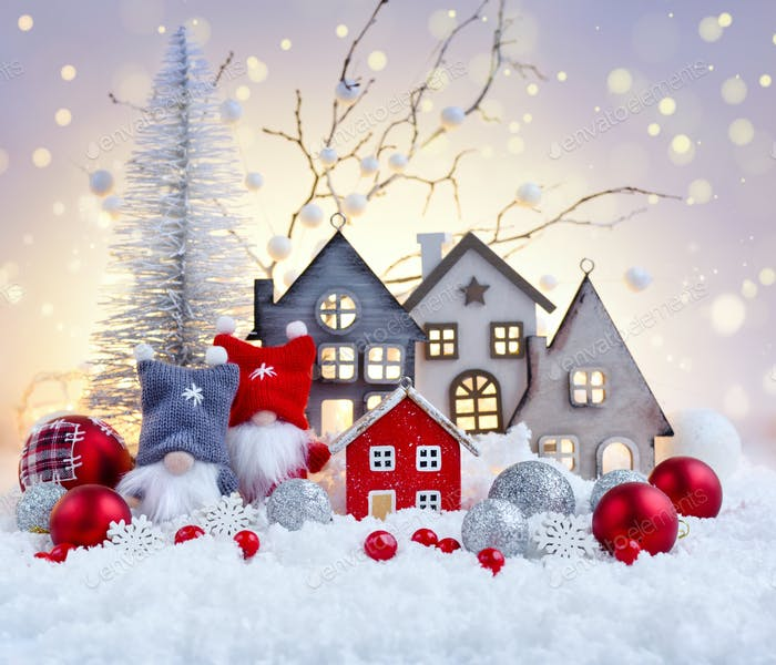 Christmas composition with gnomes, huts and festive decorations on the snow