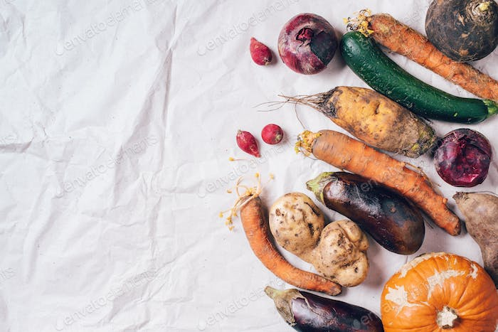 Ugly vegetables on grey background. Ugly food concept. Top view, flat lay