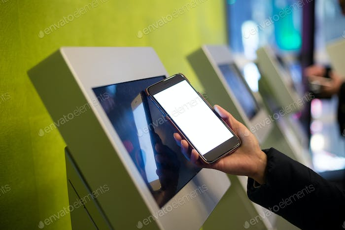 Woman using the ticketing system by cellphone with NFC technology