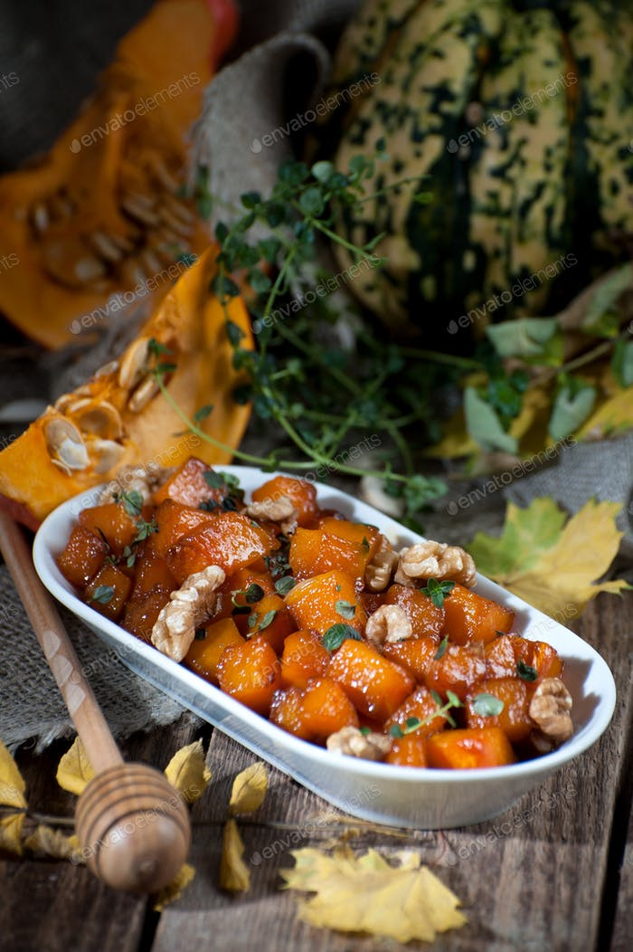 Caramelized pumpkin with honey, nuts and thyme leaves. Shooting