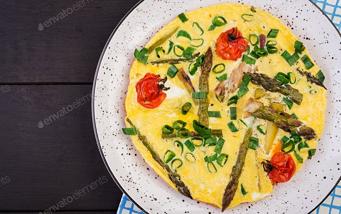 Omelette with asparagus and tomato for breakfast on a wooden background. Top view