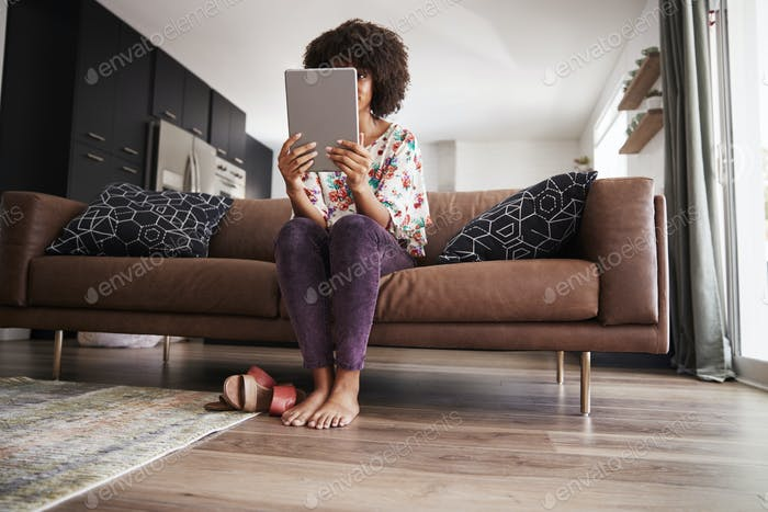 Woman Sitting On Sofa At Home Using Digital Tablet