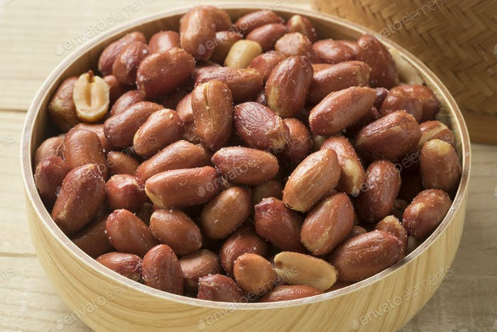 Wooden bowl with salted peanuts