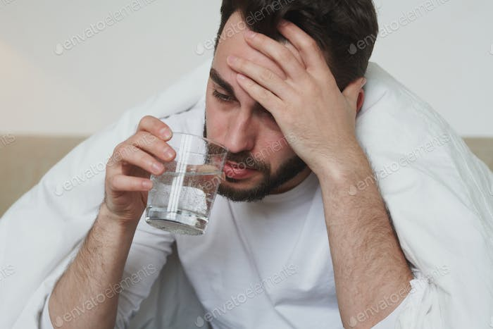 Unhappy young man with covid19 or flu touching his forehead and drinking water