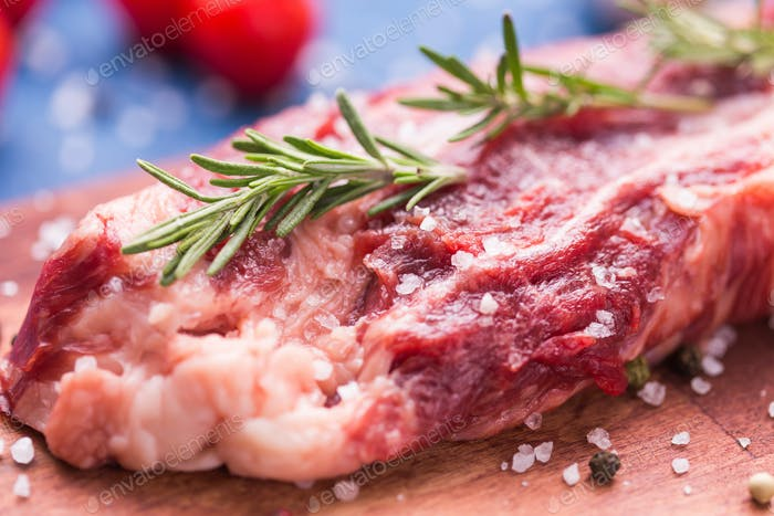 Fresh raw meat for steak on wooden cutting board, close-up.