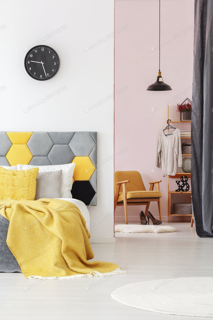 Yellow bedroom interior with clock