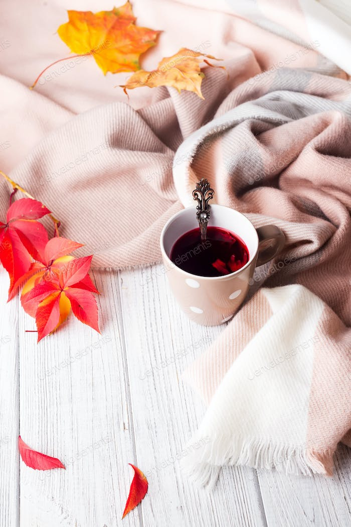 A cup of healthy tea in yellow red leaves with beige scarf on white wooden background, copy space