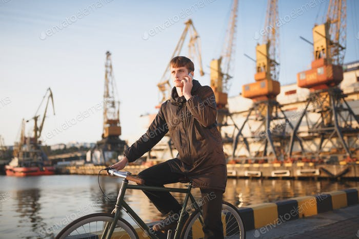 Cool boy in down jacket on bicycle standing with sea port on background