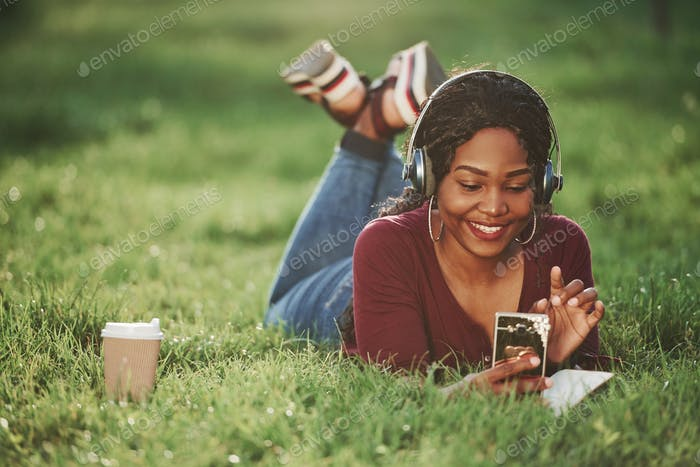 Watching funny content. Cheerful african american woman in the park at summertime
