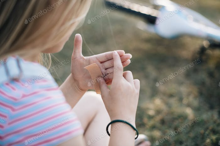 Young girl applying a bandage to her palm