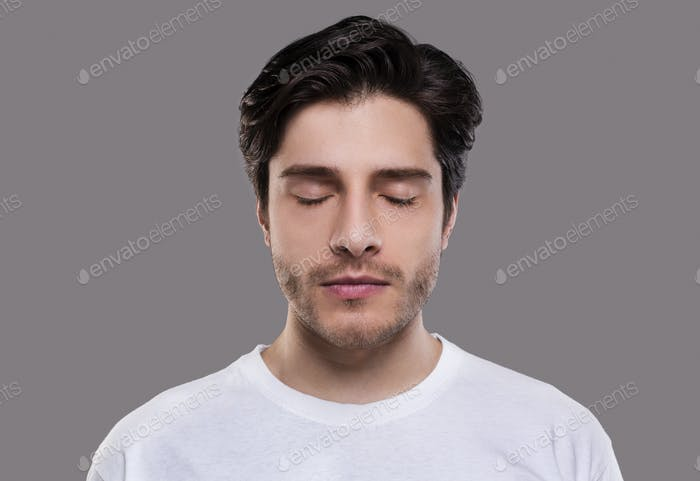 Portrait of handsome millennial man with closed eyes