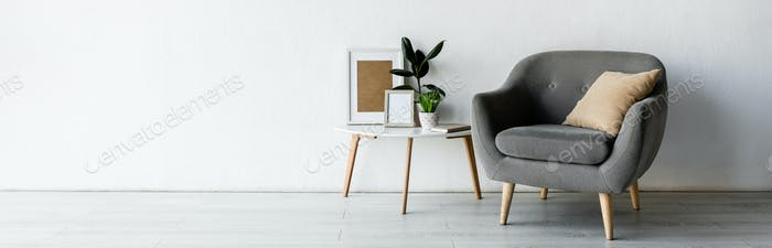 panoramic orientation of comfortable armchair near coffee table with green plants and frames in