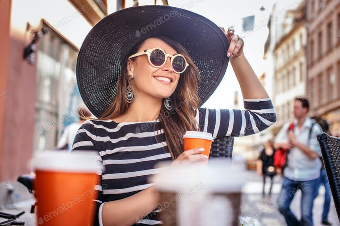 Elegantly dressed young woman wearing a stylish hat and sunglasses sitting in a summer street cafe