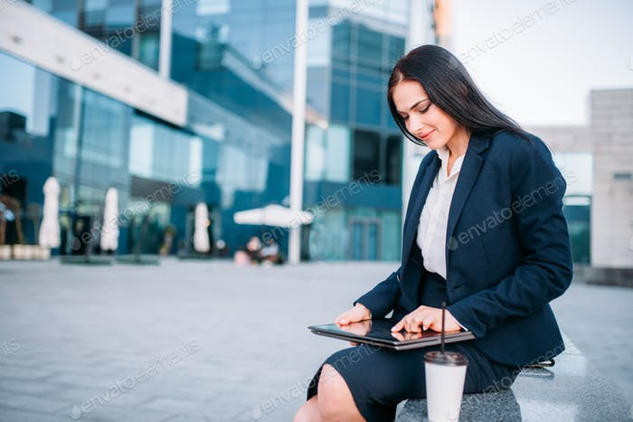 Business woman works on laptop outdoor
