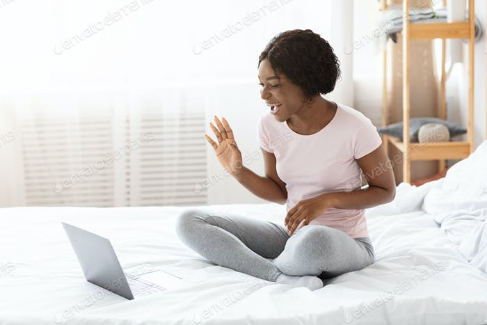 Emotional african american woman having online party with friends