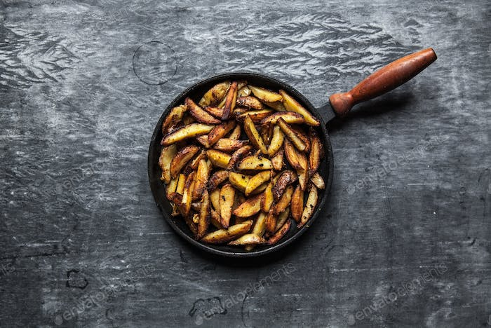 Fried hot potatoes in a pan. Dark background