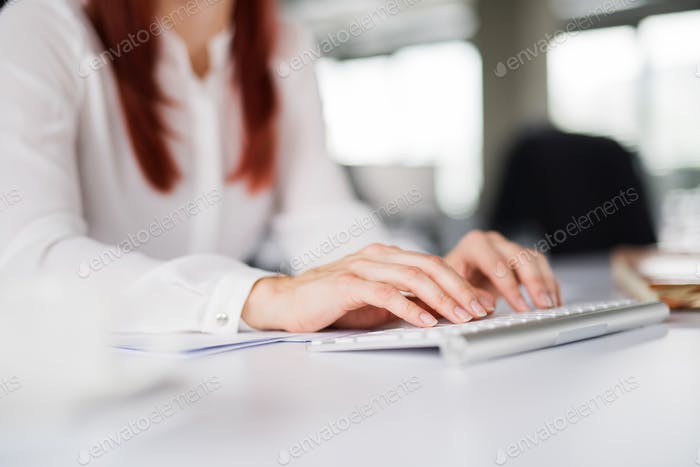 Unrecognizable businesswoman in the office writing something.
