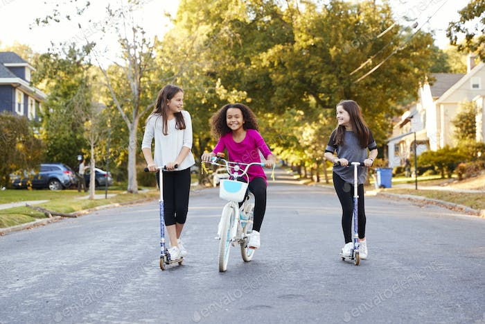 Three pre-teen girls riding in street on scooters and a bike