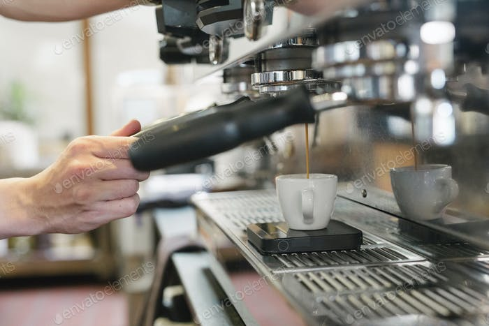 Close up of a man standing in front of an espresso machine, fresh espresso running into a cup.