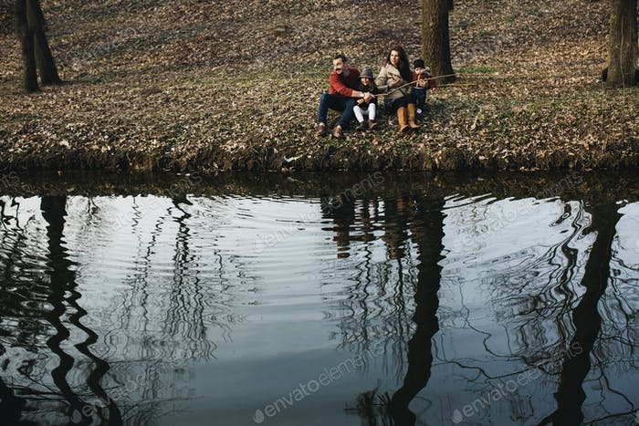 family resting on the river bank