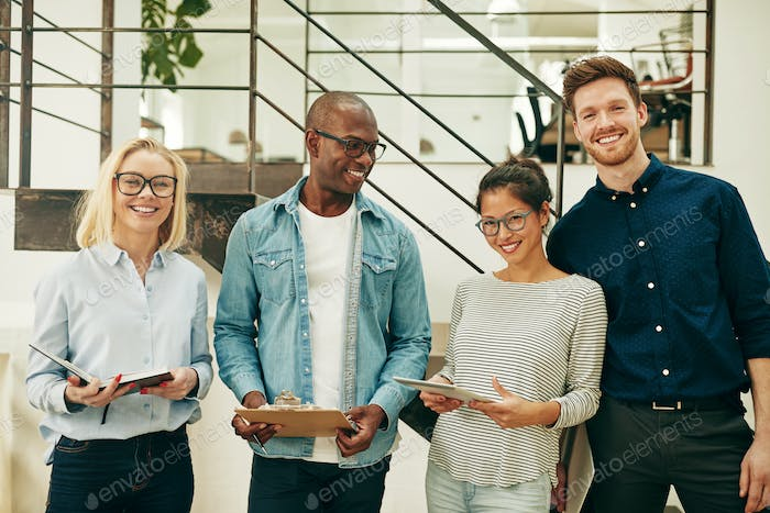 Diverse businesspeople laughing together while working in an office