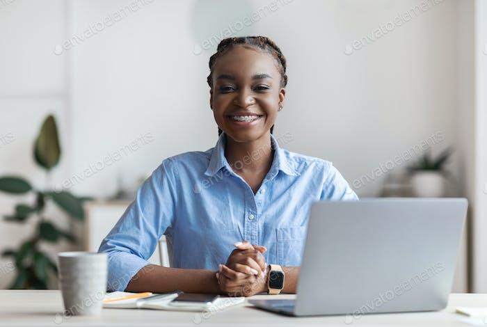 Remote-Arbeit. Glückliche junge schwarze Freiberuflerin posiert im Homeoffice