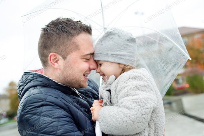 Young father holding his little daughter under the umbrella.