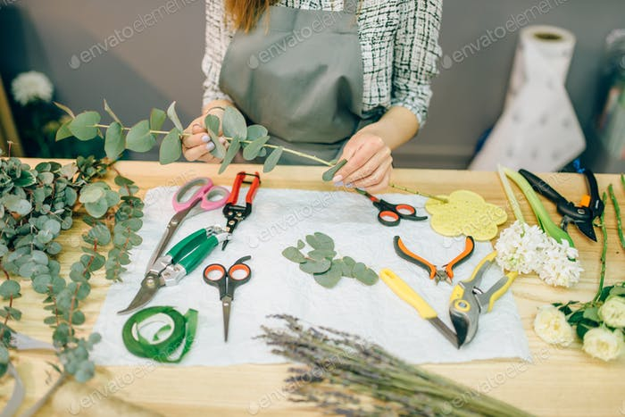 Female florist prepares rose bouquet at workplace