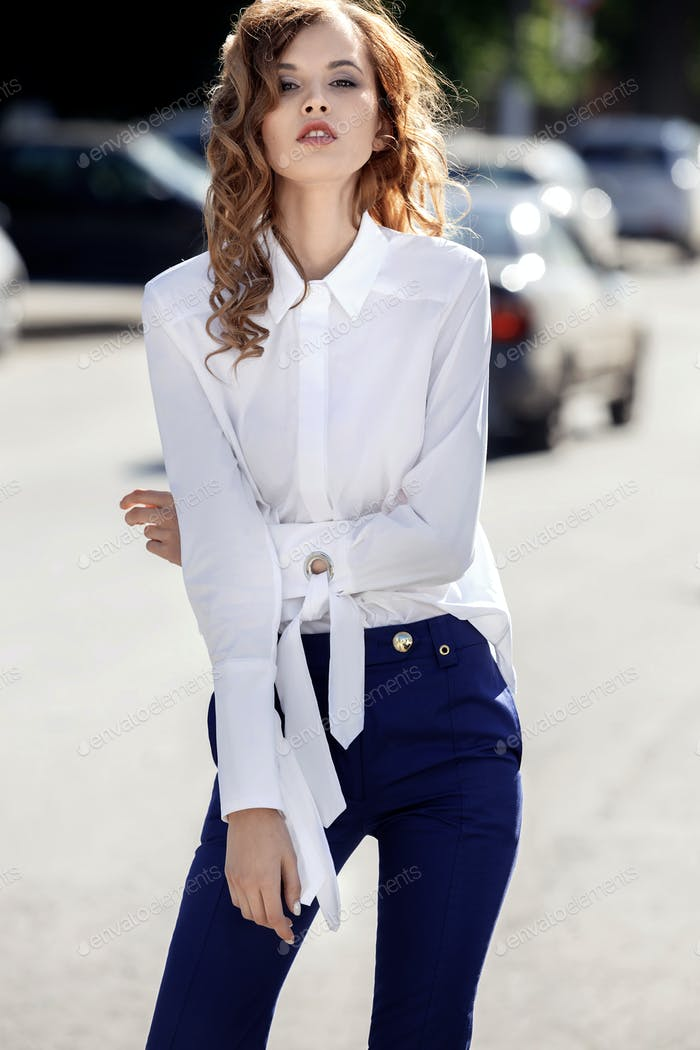 Slim stylish brunette girl dressed in white shirt and blue trousers is standing in the street on a