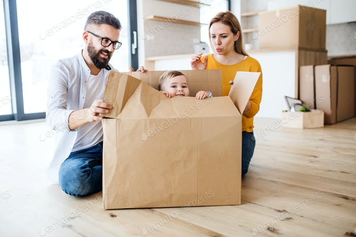 A portrait of young family with a toddler girl moving in new home.