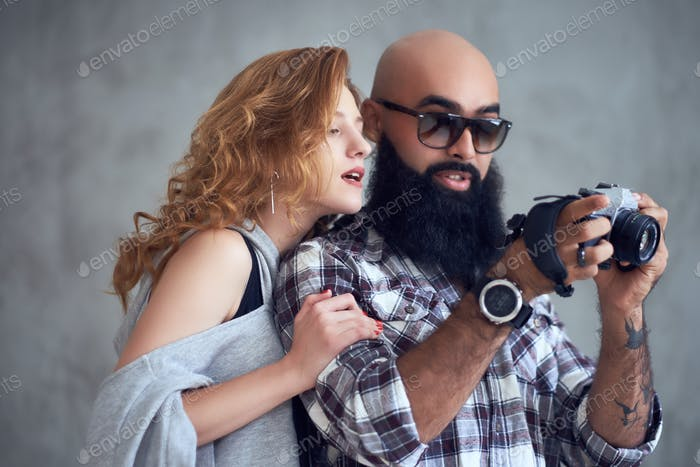 Amateur bearded photographer and a redhead female.