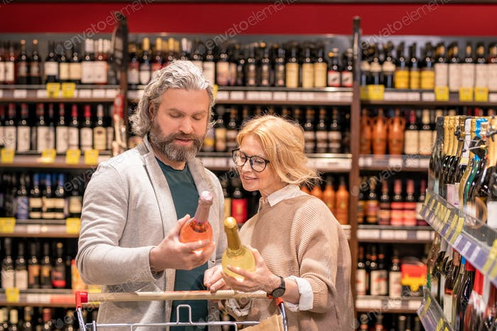 Aged bearded man with bottle of wine and his wife reading information on label
