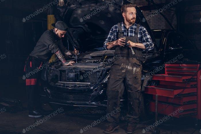 Two bearded auto mechanic working in repair garage.