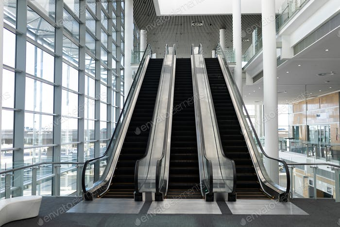 Front view of three modern escalators in a office lobby against inside buildings in background