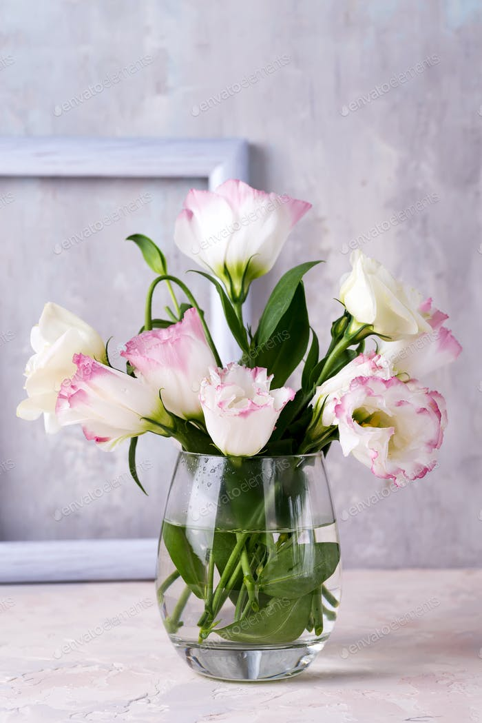 Eustoma flowers in vase on table near stone wall. Blank for postcards