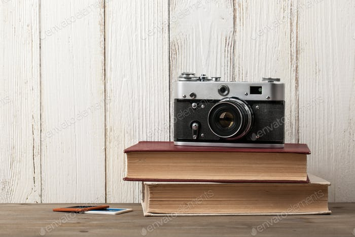Retro film camera and books on wooden table