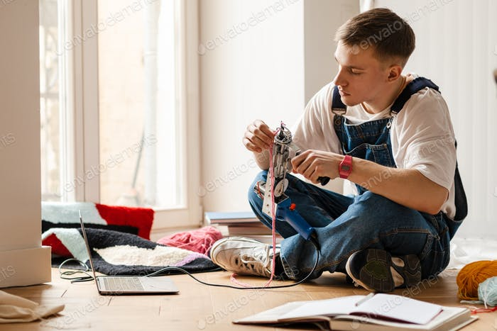 Young man using laptop and sewing machine while working on craft rug