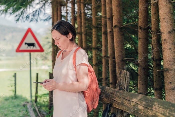Female hiker text messaging on mobile phone by the road